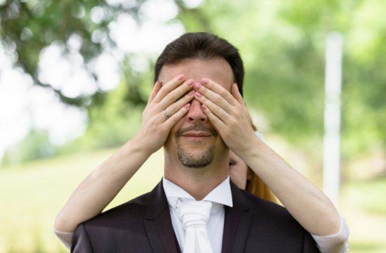les mains sur les yeux du marié lors du first look