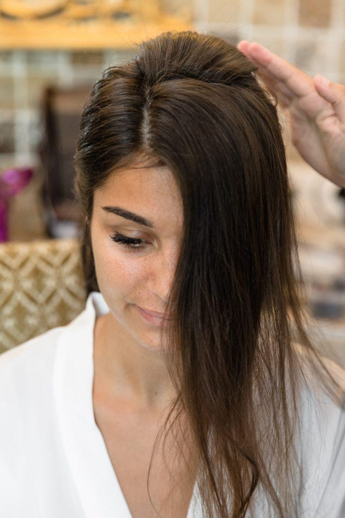 Gros plan de face sur la mariée qui se fait coiffer