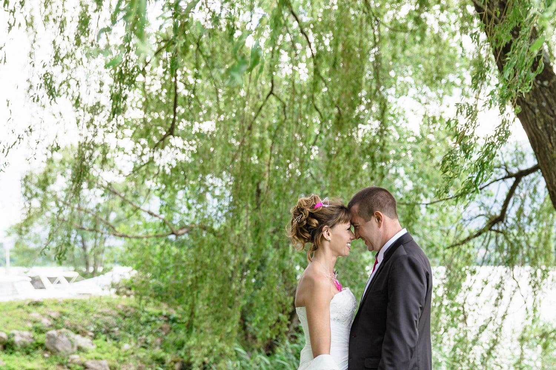 Les mariés de profil sous un sole pleureur au bord du lac du Bourget