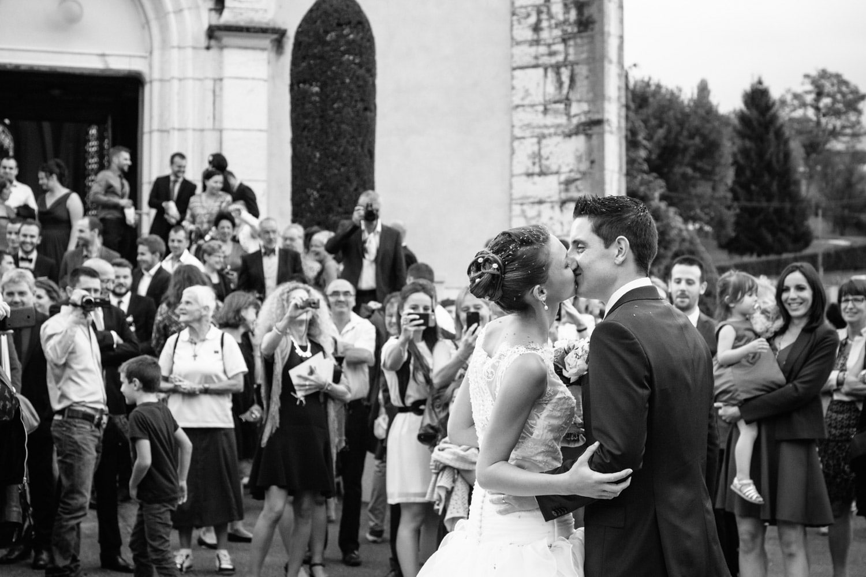 bisou des mariés de dos à la sortie de l'église