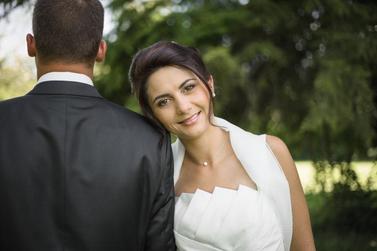 La mariée de face avec le visage sur le marié de dos